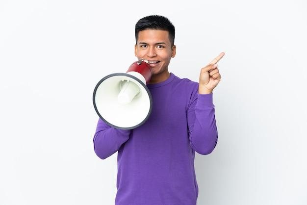 Jonge ecuadoraanse man geïsoleerd op een witte achtergrond schreeuwen door een megafoon en wijzende kant
