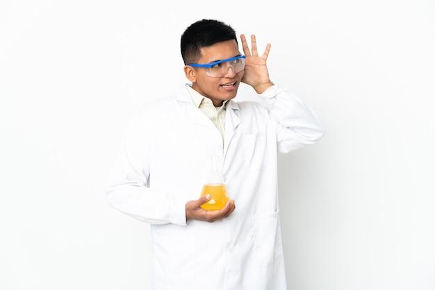 Jonge ecuadoraanse wetenschappelijke man die naar iets luistert door hand op het oor te leggen