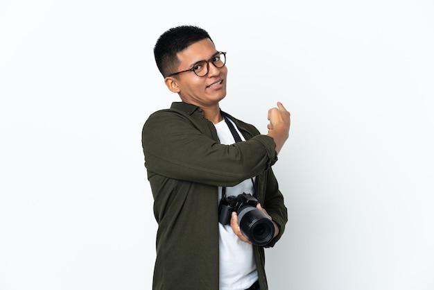 Jonge ecuadoriaanse fotograaf geïsoleerd op een witte achtergrond terug te wijzen