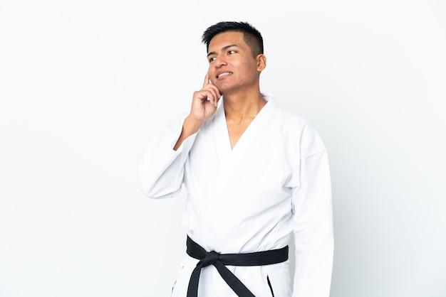 Jonge ecuadoriaanse man doet karate geïsoleerd op een witte achtergrond een idee denken terwijl opzoeken