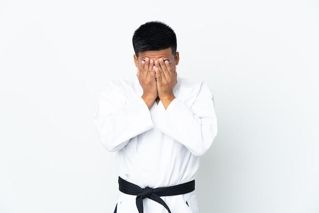 Jonge ecuadoriaanse man doet karate geïsoleerd op een witte achtergrond met vermoeide en zieke uitdrukking