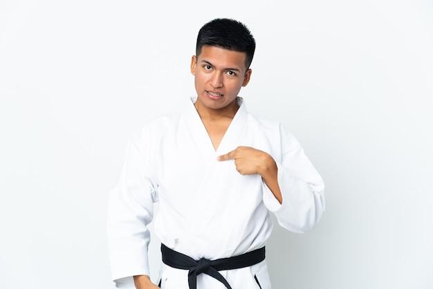 Jonge ecuadoriaanse man doet karate geïsoleerd op een witte achtergrond met verrassingsgelaatsuitdrukking