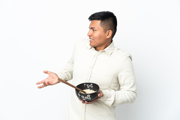 Jonge ecuadoriaanse man geïsoleerd op een witte achtergrond met verrassende gelaatsuitdrukking terwijl hij een kom noedels met stokjes vasthoudt