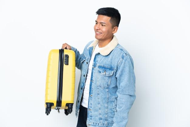 Jonge ecuadoriaanse man geïsoleerd op een witte muur in vakantie met reiskoffer