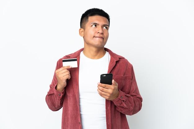 Jonge ecuadoriaanse man geïsoleerd op een witte muur te kopen met de mobiele telefoon met een creditcard tijdens het denken