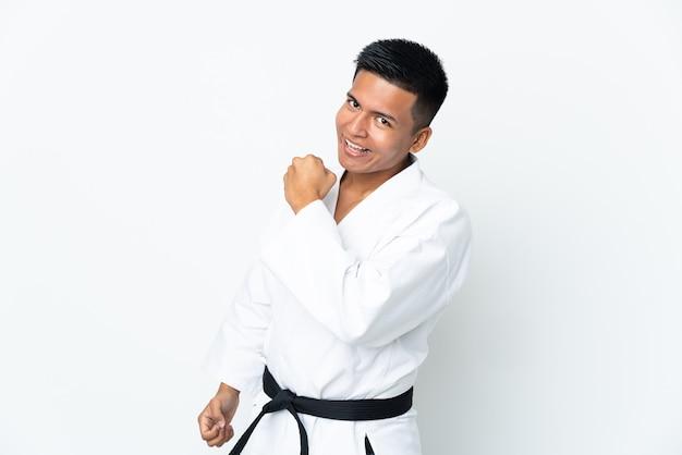 Jonge ecuadoriaanse mens die karate doet die op witte muur wordt geïsoleerd die een overwinning viert