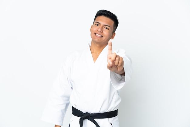 Jonge ecuadoriaanse mens die karate doet die op witte muur wordt geïsoleerd die en een vinger opheft