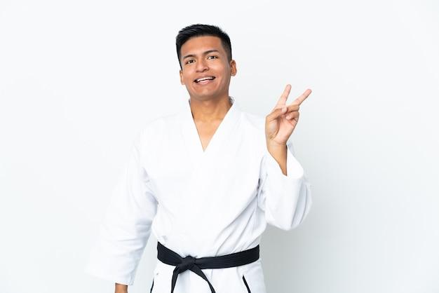 Jonge ecuadoriaanse mens die karate doet die op witte muur wordt geïsoleerd die en overwinningsteken glimlacht toont