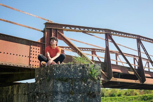 Jonge eenzame mannelijke wandelaar zitten in de buurt van de brug
