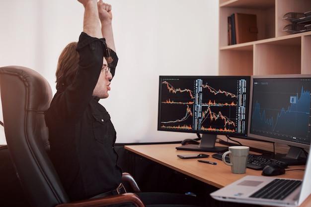 Jonge effectenhandelaar die handen uitrekt op de werkplek, hij behaalde eerst groot succes op de aandelenmarkt