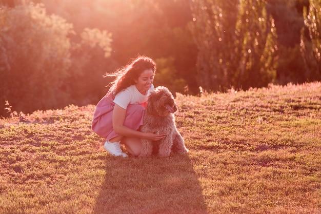 Jonge eigenaarvrouw met haar bruine spaanse waterhond die pret in openlucht in een park hebben bij zonsondergang. liefde voor dieren concept