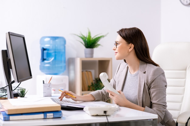 Jonge eigentijdse bureaumanager of hoofd van bedrijf dat door bureau voor computerscherm zit en telefoonontvanger vasthoudt