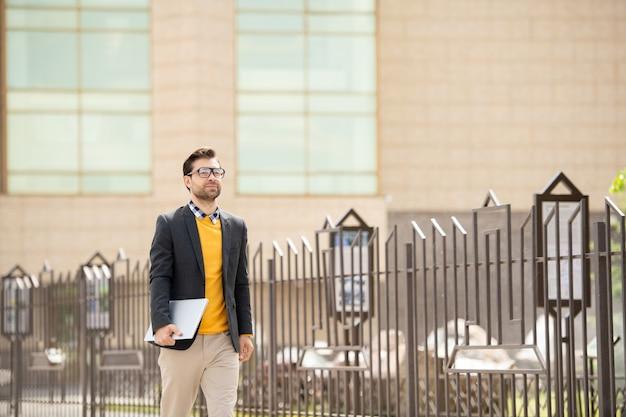 Jonge eigentijdse elegante man met gevouwen laptop die zich in de ochtend langs het hek in de stedelijke omgeving beweegt