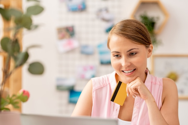 Jonge eigentijdse vrouw met plastic kaart kijken door goederen in online winkel terwijl bestelling gaat maken