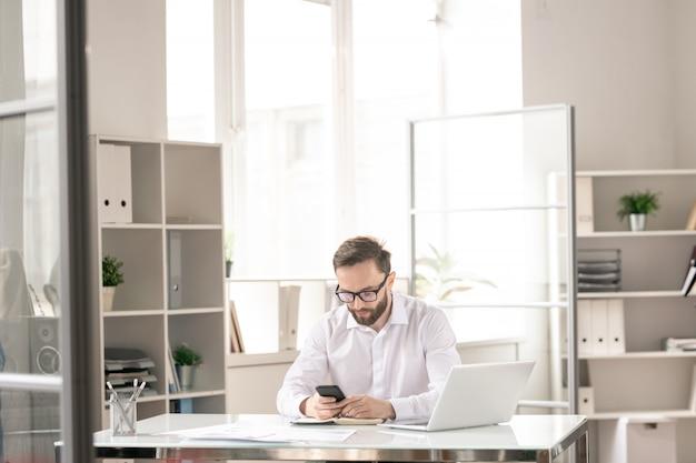 Jonge eigentijdse zakenman zit door bureau in kantoor en sms'en of scrollen in smartphone op het werk