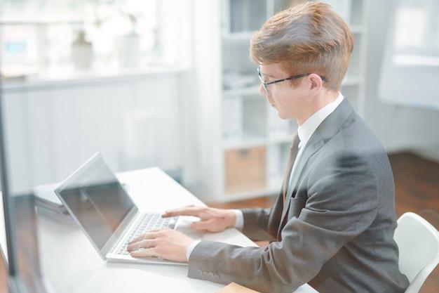 Jonge elegante advocaat die laptop gebruikt voor het zoeken van online gegevens over nieuwe wetten in het net