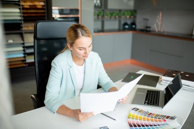 Jonge elegante blonde onderneemster die de tekst van het contract op twee documenten leest alvorens het te ondertekenen