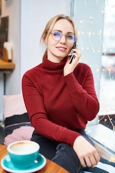 Jonge elegante blonde vrouw in brillen en casual donkerrode trui zitten door tafel in café en praten door smartphone