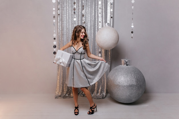 Jonge, elegante dame op hoge hakken houdt een doos met een nieuwjaarscadeau vast en raakt flirterig haar schitterende prachtige jurk aan