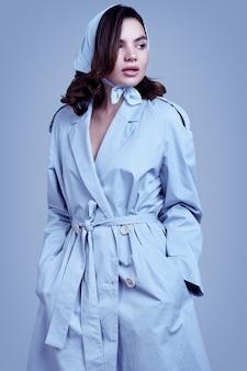 Jonge elegante donkerbruine vrouw in jas en sjaal het stellen in studio