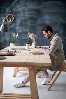 Jonge elegante drukke student notities maken zittend aan tafel en huiswerk voorbereiden in de klas op de universiteit