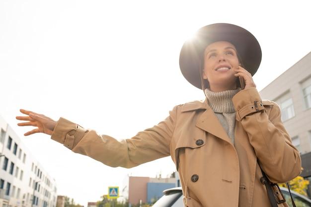 Jonge elegante glimlachende zakenvrouw in beige trenchcoat en zwarte hoed die taxi probeert te vangen terwijl ze over de weg in een stedelijke omgeving staat