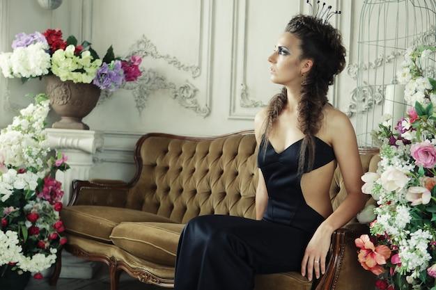 Jonge elegante koningin in zwarte jurk