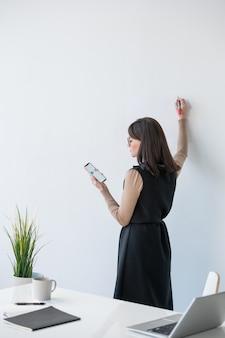 Jonge elegante leraar permanent door whiteboard, smartphonescherm kijken en presentatie gaan maken