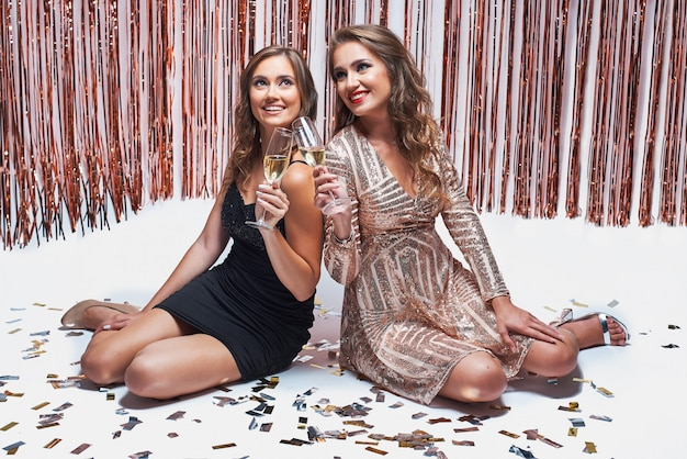 Jonge elegante meisjes die pret hebben en champagne drinken tijdens nieuwjaarpartij.