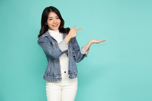 Jonge elegante mooie aziatische vrouw glimlachend en wijst naar lege kopie ruimte geïsoleerd op groene achtergrond