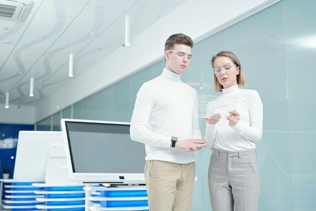 Jonge elegante officemanager in slimme bril presentatie van nieuwe ultramoderne transparante tablet maken aan client en laten zien hoe te gebruiken