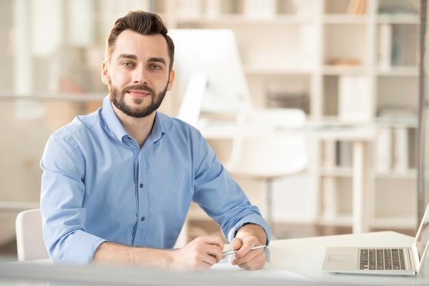 Jonge elegante officemanager of adviseur in bureau zitten
