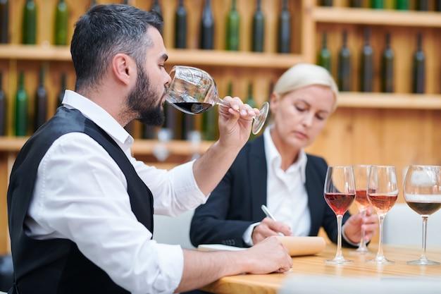 Jonge elegante sommelier die rode wijn proeft uit een van de glazen om de kwaliteit en smaak te controleren
