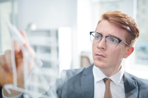 Jonge elegante student in pak en bril transparant bord kijken tijdens het opschrijven van punten van seminar