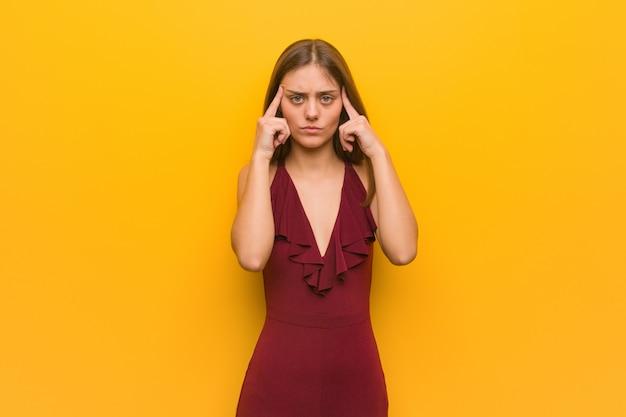 Jonge elegante vrouw die een kleding draagt die een concentratiegebaar doet