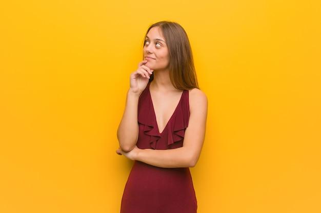 Jonge elegante vrouw die een twijfelende en verwarde jurk draagt