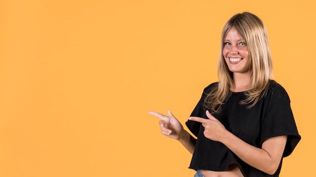 Jonge elegante vrouw die op een gele achtergrond richt