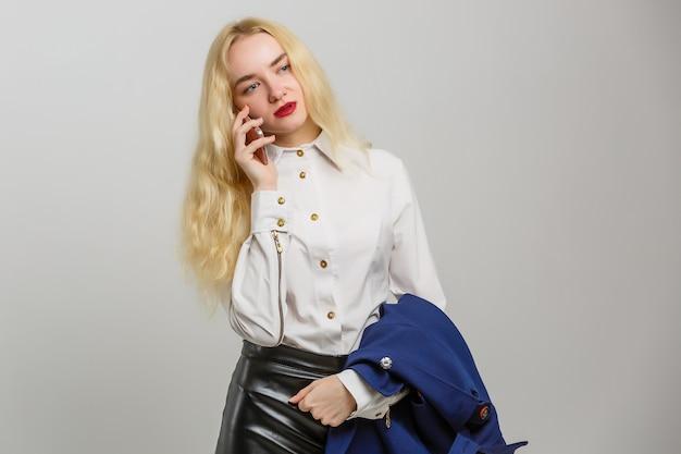 Jonge elegante vrouw die op mobiele telefoon tegen witte achtergrond spreekt