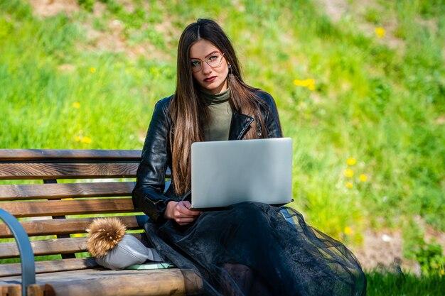 Jonge elegante vrouw in oogglazen die op bank in park zitten en aan laptop op een zonnige en winderige dag werken
