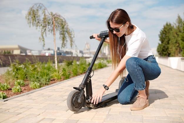 Jonge elegante vrouw in vrijetijdskleding en zonnebril staande op knie tijdens het controleren van de motor van de elektrische scooter op weg naar haar werk