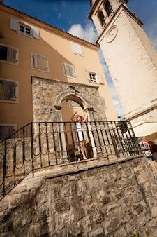 Jonge elegante vrouw in witte hoed die zich voordeed op oude stenen trappen in de stad budva, montenegro