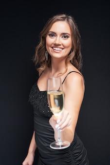 Jonge elegante vrouw met glas champagne op feestje.