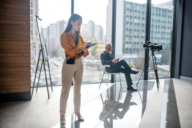 Jonge elegante vrouwelijke verslaggever die zich in de studio bevindt die druk kijkt