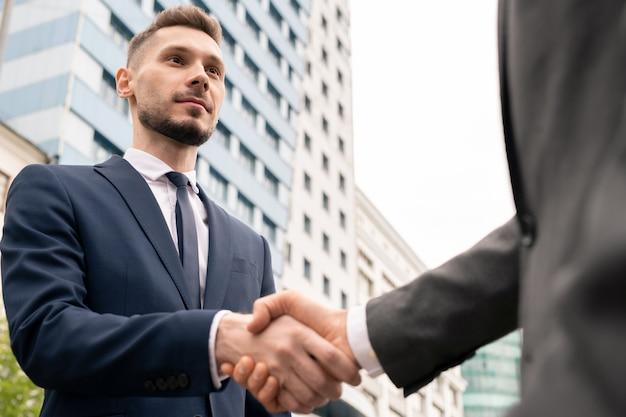 Jonge elegante zakenman hand van cliënt schudden na het onderhandelen en ondertekenen van contract tijdens openluchtvergadering