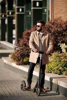Jonge elegante zakenman met elektrische autoped die zich door groene vegetatie bevindt die door modern zakencentrum in openlucht groeit