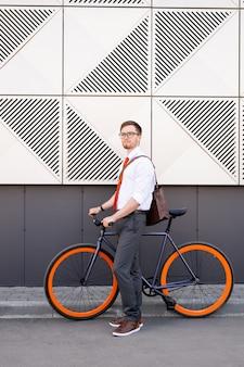 Jonge elegante zakenman met fiets die zich op asfaltweg tegen muur van modern gebouw met zwarte en witte tegels bevindt