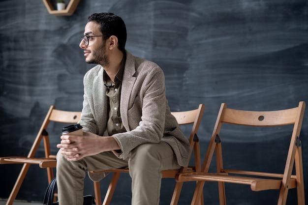 Jonge elegante zakenman met glas koffie zittend op een stoel in moderne café op de ruimte van het bord