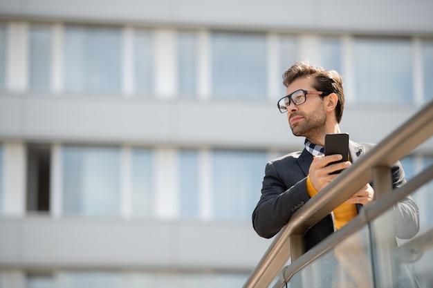 Jonge elegante zakenman met smartphone leunend door balustrades door modern kantoorgebouw of zakencentrum