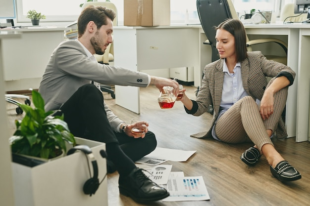 Jonge elegante zakenman whisky gieten in wijnglas gehouden door zijn vrouwelijke collega over financiële papieren op de vloer in kantoor
