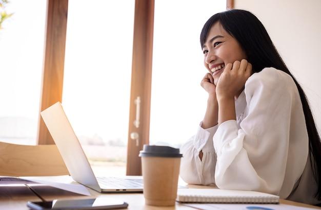 Jonge elegante zakenvrouw in wit overhemd en kopje koffie zitten met laptop in café. dromen positief denkende persoon concept.